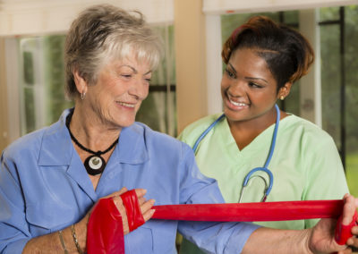 Medical:  Home healthcare nurse helps woman with band therapy.
